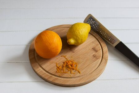 Orange Lemon zest cutting board grater background. Stock Photo - 133334681