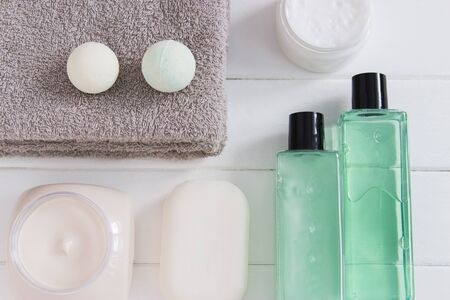 Womens beauty concept products gray towels flatlay.