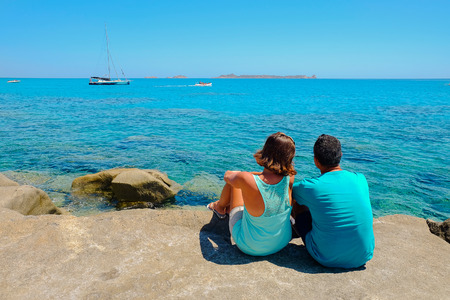 A man and a woman sitting on the stone beach and watching the sea with emerald water and white boats.