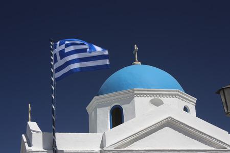 myconos: Orthodox church and Greek flag in Greece. Stock Photo
