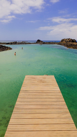 oliva: View on the wooden catwalk and lagoon with green water, unknown swimmers and volcanic rocks. Location Canary island Lobos, Fuerteventura, Spain. Stock Photo