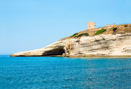 View on blue sea and the tower on the rock in Santa Caterina di Pittinuri in Sardinia, Italy.
