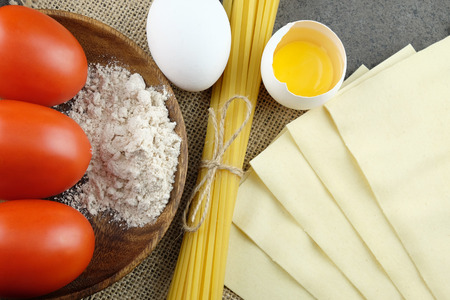 Basic ingredients for cooking the Italian pasta on a dark rural background: bavette, lasagne sheets, fresh tomatoes, eggs and wheat.