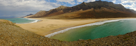 Beautiful landscape on the beach Cofete with green ocean color, yellow sand and mountains on the Canary Island Fuerteventura, Spain. Panorama format.