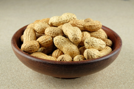Peanuts in a wooden bowl on natural background.