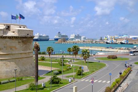 Vista sul porto con tre grandi navi a Civitavecchia, una strada e una torre del Forte Michelangelo - Civitavecchia - Italia. Archivio Fotografico - 80169075
