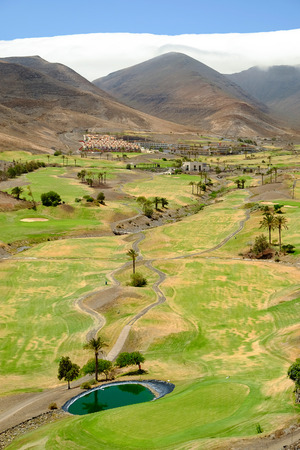 View on the green field for golf between the mountains, a beautiful white cloud and blue sky on the Canary Island Fuerteventura, Spain. Stock Photo