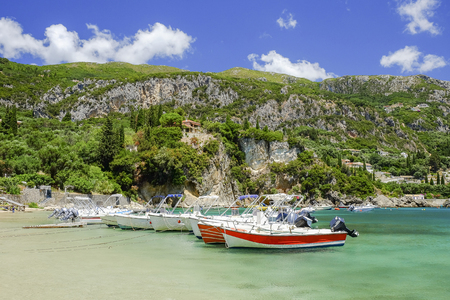 paleokastritsa: View on mountains with green vegetation, emerald sea water and boats in a small harbor in Paleokastritsa on the island Corfu in Greece.
