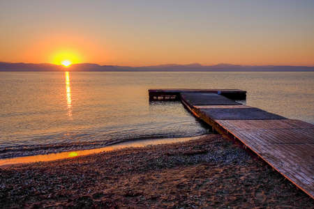 View on the sunrise on the sea, the mountains and a wooden pier on the beach Moraitika, island Corfu, Greece.