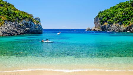 paleokastritsa: View on the beach Paleokastritsa with unknown tourists paddling on the island Corfu in Greece.