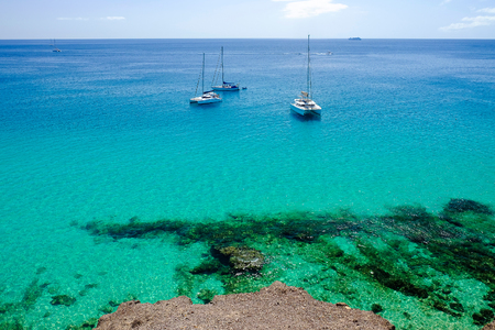 View on the ocean with crystal water and three woutistic boats in Morro Jable on the Canary island Fuerteventura, Spain.