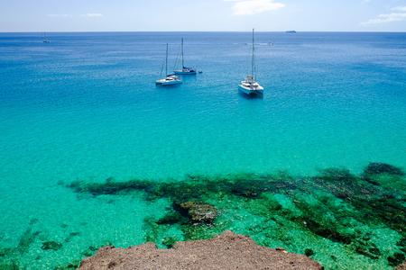 Ansicht über den Ozean mit Kristallwasser und drei woutistic Booten in Morro Jable auf der Kanarischen Insel Fuerteventura, Spanien.