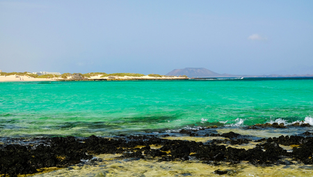 View on the island Lobos from the beach Corralejo on the Canary Island Fuerteventura, Spain. Green ocean water, yellow sand and black volcanic stones typical for the Canarias.