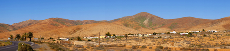 Typical landscape with curved road in red volcanic mountains and a small village close to betancuria on the Canary Island Fuerteventura, Spain. Panorama.