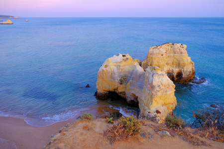 View on beautiful rock with caves on the beach Praia de Rocha in Portimao, Algarve, Portugal on the sunset.