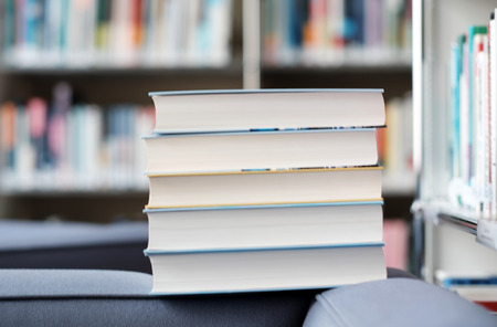 Stack of books on a couch in a library. Imagens