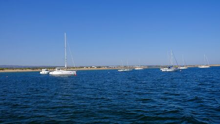 View on the blue lagoon with white sailboats in Tevira, Algarve, Portugal.