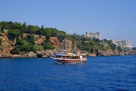 ANTALYA, TÜRKEI - Juli 0'4'' 2019: Blick vom Meer auf ein touristisches Boot und eine Küste von Antalya. Editorial