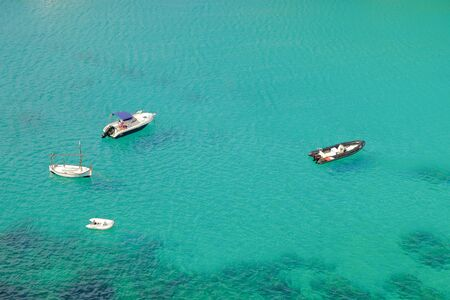 View on the green sea water with white boats in En Porter on Menorca, Balearic Islands, Spain.