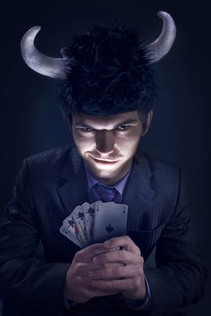 dark studio portrait of an evil man in a hat with horns and a cards