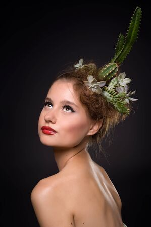 Woman with cactus in her hair on a black background photo