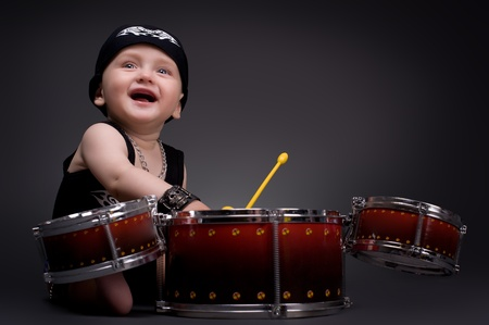 band instruments: dark portrait of  Beautiful boy playing the drums on a black background