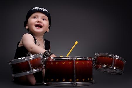 ritme: donkere portret van mooie jongen spelen de drums op een zwarte achtergrond Stockfoto
