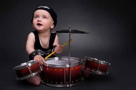 rock hand: ritratto scuro del bel ragazzo a suonare la batteria su sfondo nero