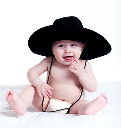 big smile: portrait of baby in a big hat on a white studio background
