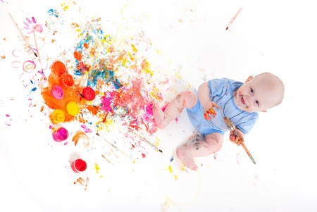 smudgy: Full-length portrait of a cheerful grimy kid. playing with paint. on a white studio background.