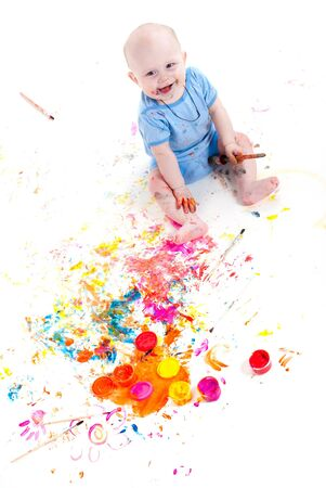 smudgy: portrait of a cheerful grimy kid. playing with paint. on a white studio background.   Stock Photo