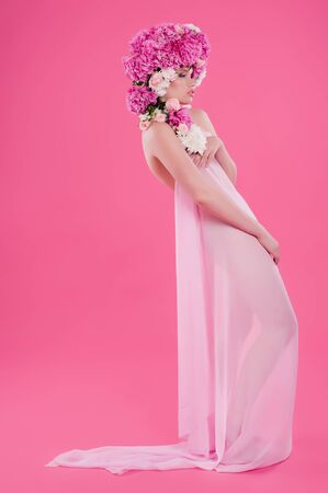 Full-length portrait of Beautiful young woman with peony flower photo