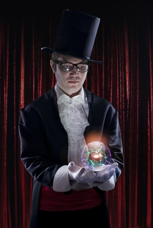 supernatural power: dark portrait of the magician on stage. Holding a luminous sphere.