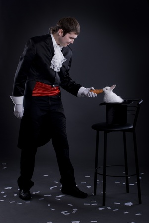 mago: hombre vestido como un mago sacando un conejo de su sombrero