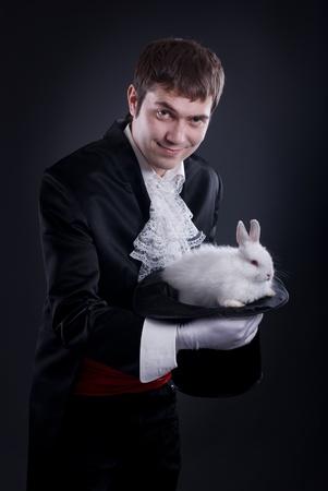 sombrero de mago: hombre vestido como un mago sacando un conejo de su sombrero