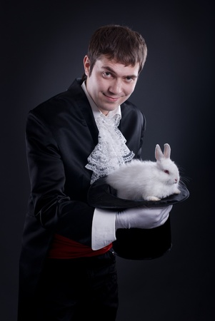 man dressed as a magician pulling a rabbit from his hat photo