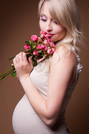 Photo portrait of a lovely young pregnant woman in a photo studio. Stock Photo