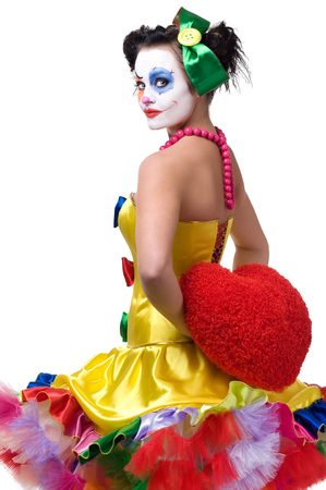 Adult female clown holding red heart behind his back