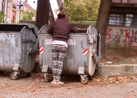 Poor woman digging out of garbage