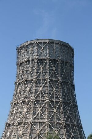 Steam going out of a cooling tower of a coal power plant into blue sky