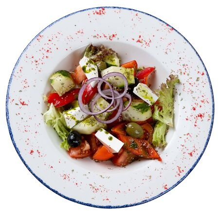 Greek salad in a round dish on a white background. Salad of tomatoes, cucumbers, cheese, herbs, seasoned with oil Reklamní fotografie
