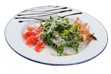 Salad with arugula and shrimp on a white background isolated. The photo was taken at an angle.