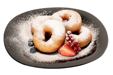 Juicy fresh donuts covered with powdered sugar on a black plate with berries on a white isolated background