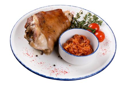 Pork knuckle with tomatoes and sauerkraut on a round light plate with a blue border, on a white isolated background, a view at an angle. Zdjęcie Seryjne