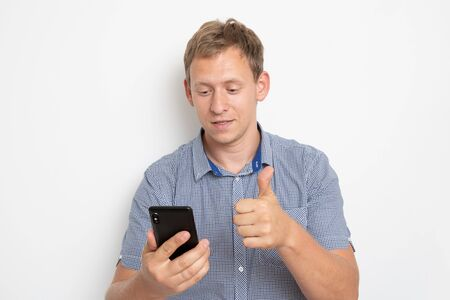 Daylight Portrait of young European Caucasian isolated on white background wearing blue shirt standing in front of camera, with phone in hand and smiling
