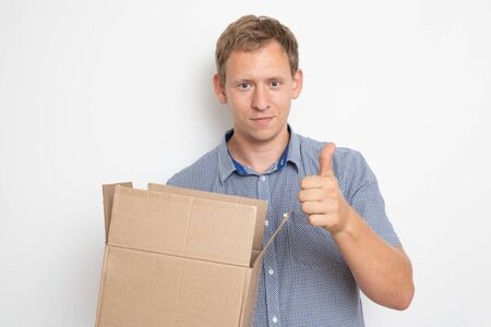 curious man looking inside a cardboard box he holds in his hands on a white background