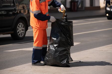 The janitor takes the trash out of the street urn and puts it in a big black bag