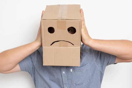 a man with a cardboard box on his head, a sad smiley 免版税图像