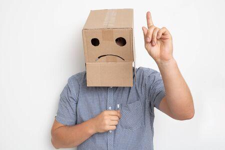 un hombre con una caja de cartón en la cabeza, una carita triste