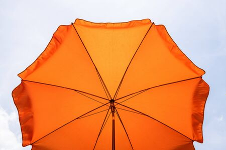 Photo of a beach umbrella on the blue sky,Beach umbrella.One vibrant orange colored sunshade against vivid blue sky and white cloud.